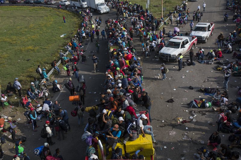 Central American migrants, part of the caravan hoping to reach the U.S. border, get a ride on a passing truck, in Irapuato, Mexico, Monday, Nov. 12, 2018. Several thousand Central American migrants marked a month on the road Monday as they hitched rides to the western Mexico city of Guadalajara and toward the U.S. border. (AP Photo/Rodrigo Abd)