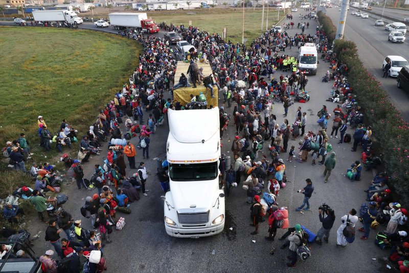 Central American migrants, part of the caravan hoping to reach the U.S. border, look from an overpass as others attempt to get a ride on trucks, in Irapuato, Mexico, Monday, Nov. 12, 2018. Several thousand Central American migrants marked a month on the road Monday as they hitched rides toward the western Mexico city of Guadalajara. (AP Photo/Marco Ugarte)
