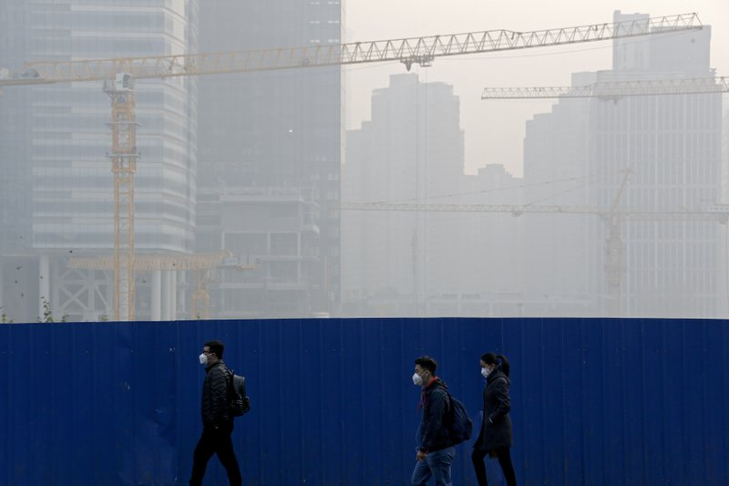 People wear masks for protection against the pollution as they walk by a construction site at the Central Business District chocked with haze in Beijing, Tuesday, Nov. 13, 2018. The potential damage to global trade brought on by President Donald Trump's tariffs battle with Beijing is looming as leaders of Southeast Asian nations, China, the U.S. and other regional economies meet in Singapore this week. (AP Photo/Andy Wong)