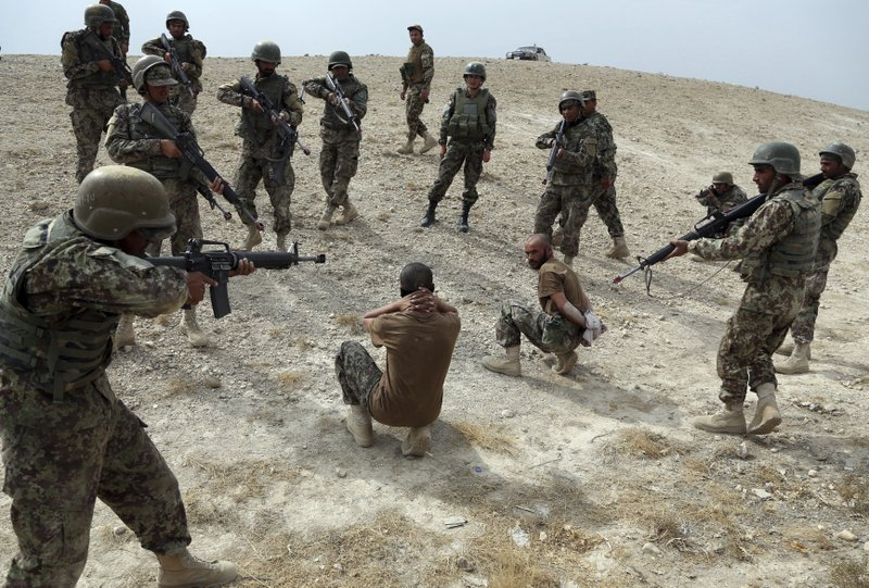 In this Oct. 31, 2018 photo, Afghan National Army soldiers make a mock arrest during a training exercise at the Afghan Military Academy in Kabul, Afghanistan. When U.S. forces and their Afghan allies rode into Kabul in November 2001 they were greeted as liberators. But after 17 years of war, the Taliban have retaken half the country, security is worse than it's ever been, and many Afghans place the blame squarely on the Americans. (AP Photo/Rahmat Gul)