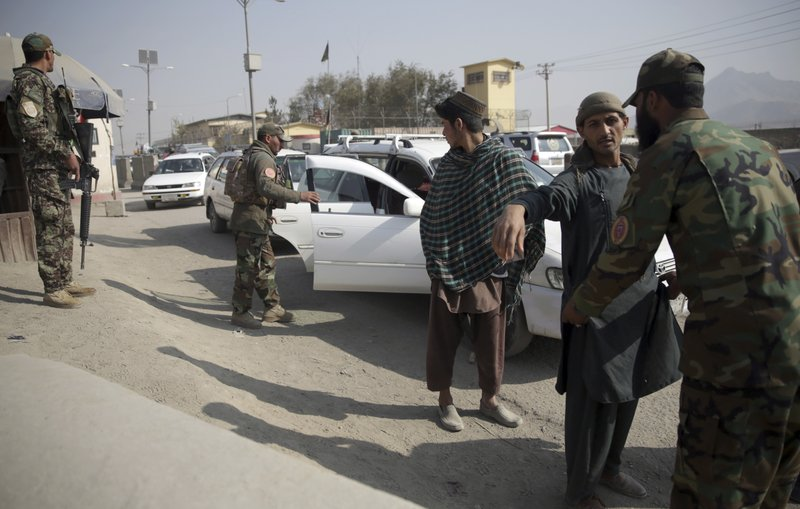 In this Oct. 26, 2018 photo, Afghan National Security Forces search passengers and their vehicles at a checkpoint in Kabul, Afghanistan. Afghans, who once welcomed Americans as liberators, now increasingly see them as the architects of their country's demise. The United States has lost more than 2,400 soldiers in its longest war and spent more than $900 billion on trying to stabilize the country.  (AP Photo/Massoud Hossaini)