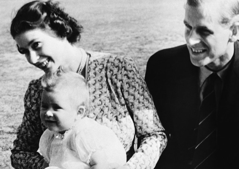 FILE - In this July 18, 1949 file photo, Britain's Prince Charles, foreground left, the eight-month-old son of Princess Elizabeth of England, left, and his father Philip, pose for a photo, on the Windlesham Moor, their summer residence, in Ascot, England. Prince Charles turns 70 Wednesday Nov. 14, 2018, still serving in the heir to the throne role he has filled since he was a young child. (AP Photo, File)