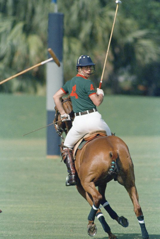 """FILE - In this Feb. 18, 1989 file photo Prince Charles looks over his shoulder as he plays in the first Prince of Wales Cup polo match at the Windsor Polo and Beach Club in Vero Beach, Fla. USA. Charles' wife, Camilla, the duchess of Cornwall wrote in a tribute ahead of Charles' birthday on Wednesday Nov. 14, 2018, in The Telegraph Magazine """"I don't think he thinks he's 70,"""" she wrote  """"I think it's just a number to him. There's no way that he will slow down. You must be joking. I keep saying 70 is getting on a bit. It's not very old but it is old. You have to slow down a bit."""" (AP Photo/Kathy Willens, File)"""