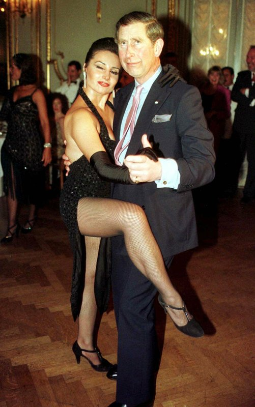 """FILE - In this Tuesday March 9, 1999 file photo Britain's Prince Charles dances the tango with Adriana Vasile, at the Presidents Dinner in Buenos Aires, during his visit to Argentina. Prince Charles turns 70 on Wednesday, Nov. 14, 2018, and is sometimes perceived as dour, preachy and remote, but his wife Camilla the duchess of Cornwall says the public doesn't understand how """"incredibly kind"""" and funny Charles is. (Peter Nichols/Pool via AP)"""
