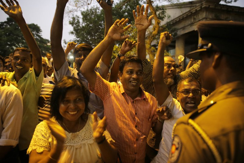 Supporters of Sri Lanka's ousted Prime Minister Ranil Wickremesinghe shout slogans as they celebrate after the Sri Lankan Supreme Court suspended dissolution of parliament by President Maithripala Sirisena, outside the court complex in Colombo, Sri Lanka, Tuesday, Nov. 13, 2018. Sri Lanka's Supreme Court has suspended a presidential decree dissolving Parliament and ruled that an earlier decree summoning lawmakers on Wednesday is valid. On Oct. 26, Sirisena abruptly ousted Wickremesinghe and replaced him with former strongman Mahinda Rajapaksa. (AP Photo/Eranga Jayawardena)