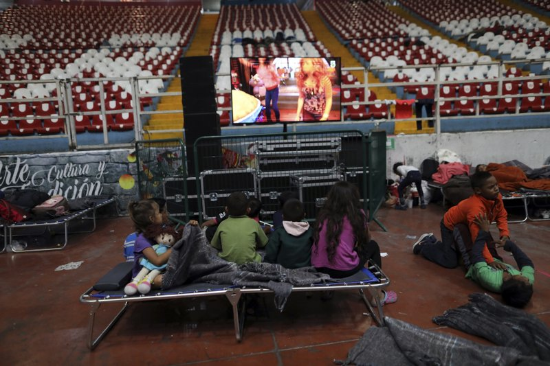 Central American children, part of the caravan hoping to reach the U.S. border, watch TV at the Benito Juarez Auditorium, used as a migrant shelter, in Guadalajara, Mexico, Monday, Nov. 12, 2018. Several thousand Central American migrants marked a month on the road Monday as they hitched rides toward the western Mexico city of Guadalajara. (AP Photo/Rodrigo Abd)