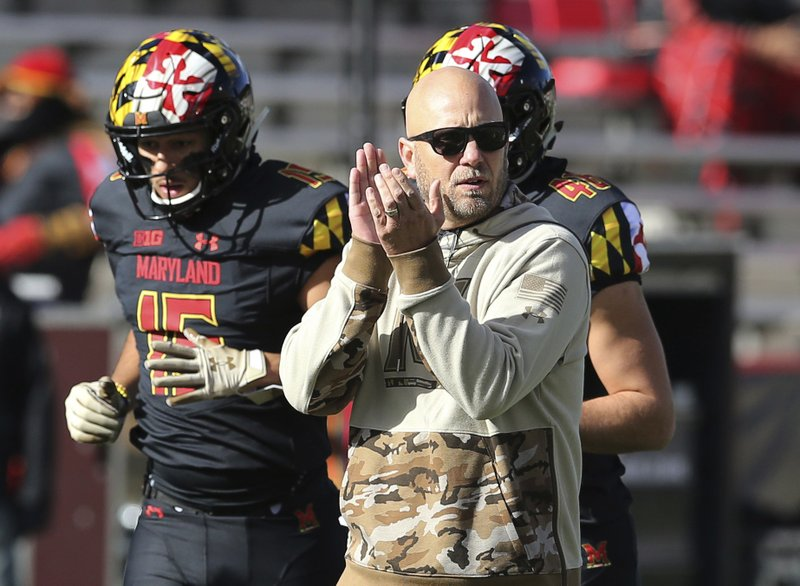 FILE - In this Nov. 3, 2018, file photo, Maryland interim head coach Matt Canada gestures while watching his team warm up before playing Michigan State in an NCAA college football game,  in College Park, Md. During a harsh season in which the Maryland football team has been forced to deal with an array of setbacks _ none worse than the death of Jordan McNair _ the Terrapins have repeatedly showed their resiliency. (AP Photo/Gary Cameron, File)