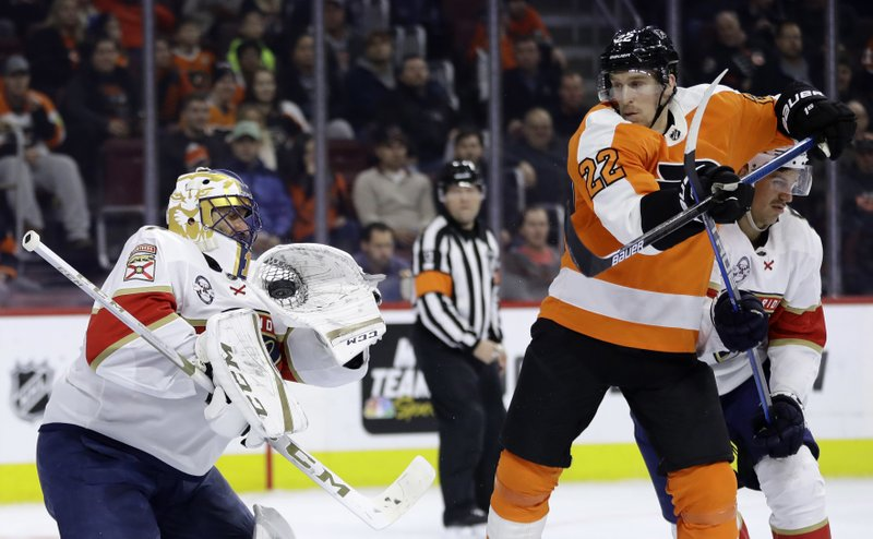 Florida Panthers' Roberto Luongo, left, catches a shot past Philadelphia Flyers' Dale Weise, center, as Alexander Petrovic defends during the second period of an NHL hockey game, Tuesday, Nov. 13, 2018, in Philadelphia. (AP Photo/Matt Slocum)
