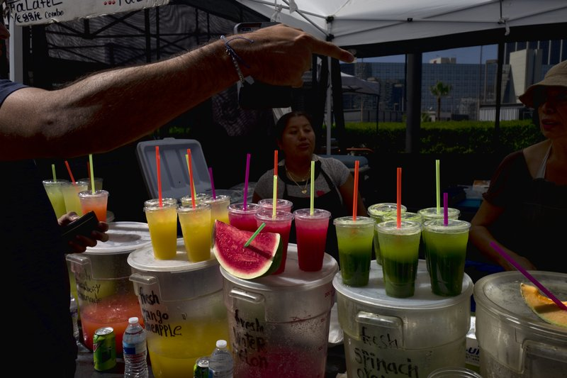 FILE - In this Sept. 21, 2018, file photo, a customer selects a drink from a vendor selling fresh juices and fruit at a farmers market in downtown Los Angeles. Avoiding single-use plastics like straws, plastic bags and water bottles is easier than it seems and can feel empowering, say those who've managed to stop using them altogether. (AP Photo/Richard Vogel, File)