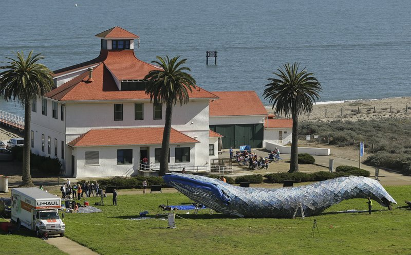 FILE - In this Oct. 12, 2018, file photo, artist Joel Deal Stockdill, lower right, works on a blue whale art piece made from discarded single-use plastic at Crissy Field in San Francisco. Artists were putting the finishing touches on the 82-foot-long (24-meter-long) blue whale made from discarded plastic that will be in display near San Francisco's Golden Gate Bridge to raise awareness about ocean pollution. (AP Photo/Eric Risberg, File)