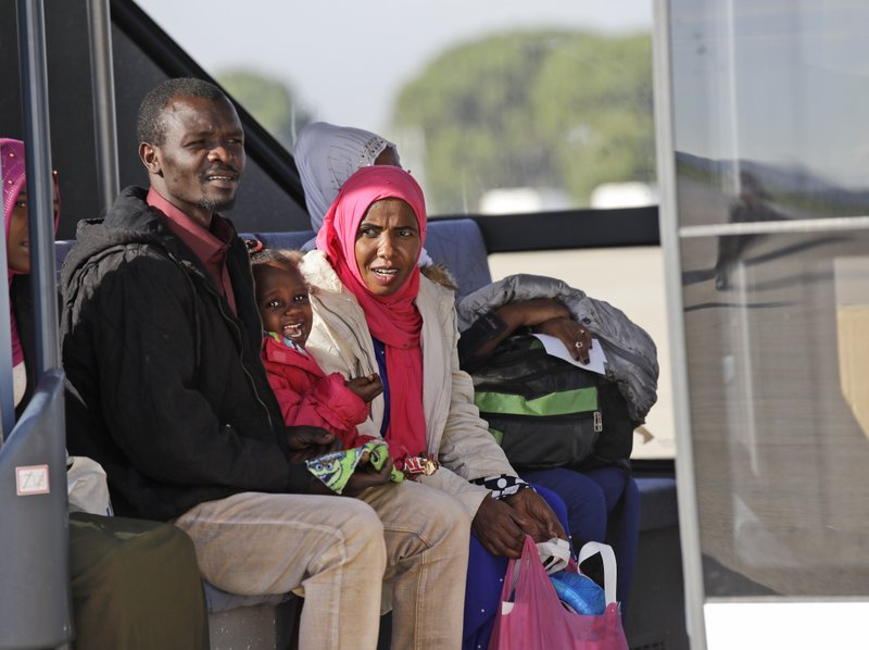 A family sits on a bus upon their arrival in Pratica di Mare's military airport, near Rome, Wednesday, Nov. 14, 2018. A group of 51 refugees and asylum seekers from Sudan, Ethiopia, Eritrea, Somalia and Cameroon, arrived in Italy from Niger, where they had been transferred to after being held in Libyan detention centers. (AP Photo/Alessandra Tarantino)