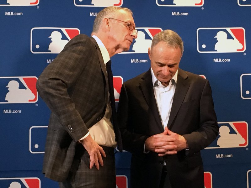 DAZN chairman John Skipper, left, speaks to Major League Baseball commissioner Rob Manfred at the baseball owners meeting in Atlanta, Thursday, Nov. 15, 2018. (AP Photo/Paul newberry)
