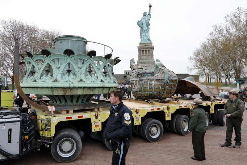 The original torch of the Statue of Liberty, and a replica of her face, rides on a hydraulically stabilized transporter, Thursday, Nov. 15, 2018 in New York. The torch, which was removed in 1984 and replaced by a replica, was being moved into what will become its permanent home at a new museum on Liberty Island. (AP Photo/Richard Drew)