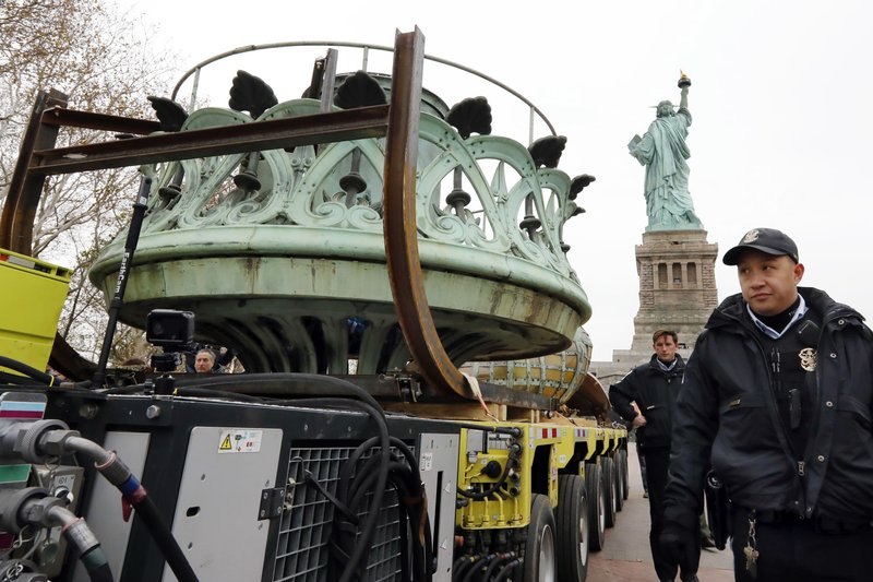 The original torch of the Statue of Liberty rides on a hydraulically stabilized transporter, Thursday, Nov. 15, 2018, in New York. The torch, which was removed in 1984 and replaced by a replica, was being moved into what will become its permanent home at a new museum on Liberty Island, background. (AP Photo/Richard Drew)