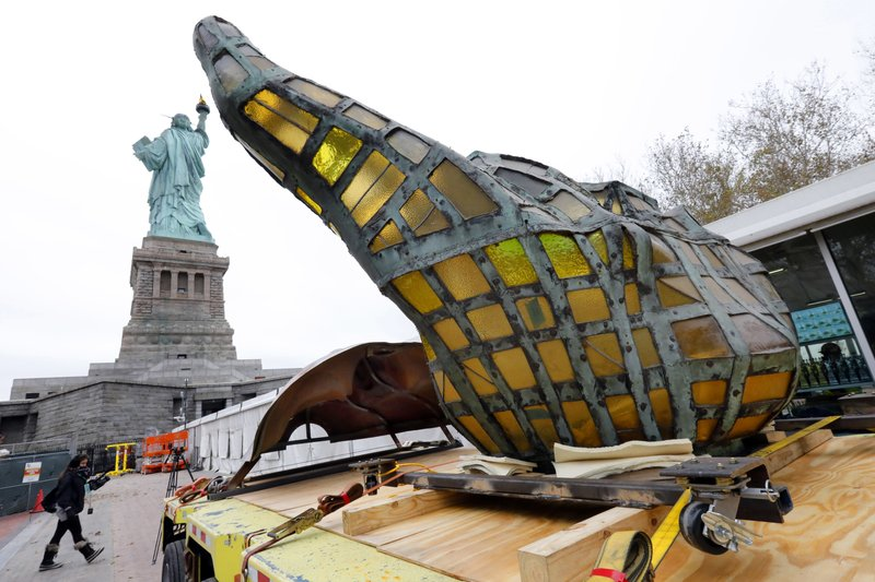 The original torch of the Statue of Liberty rests on a hydraulically stabilized transporter, Thursday, Nov. 15, 2018 in New York. The torch, which was removed in 1984 and replaced by a replica, was being moved into what will become its permanent home at a new museum on Liberty Island. (AP Photo/Richard Drew)