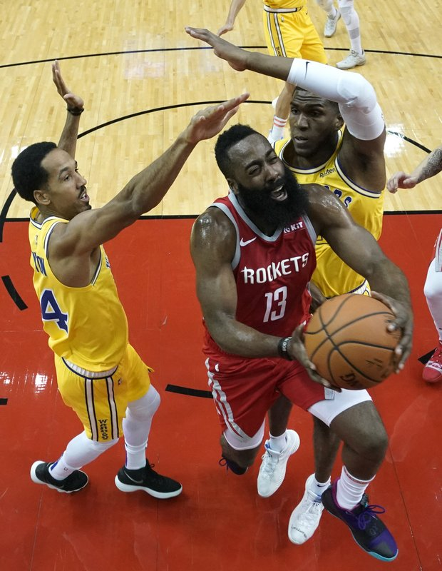 Houston Rockets' James Harden (13) goes up for a shot as Golden State Warriors' Shaun Livingston (34) and Kevon Looney defend during the first half of an NBA basketball game Thursday, Nov. 15, 2018, in Houston. (AP Photo/David J. Phillip)