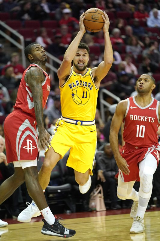 Golden State Warriors' Klay Thompson (11) drives toward the basket as Houston Rockets' Eric Gordon (10) and Gary Clark defend during the first half of an NBA basketball game Thursday, Nov. 15, 2018, in Houston. (AP Photo/David J. Phillip)