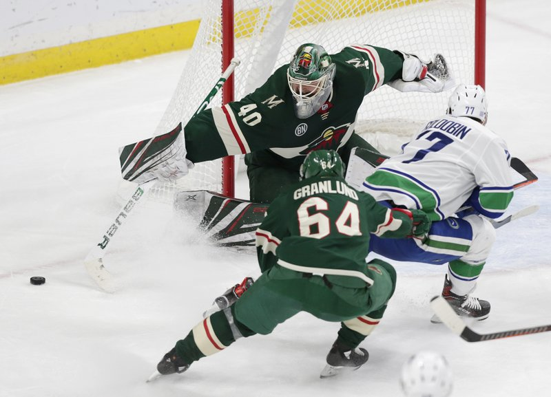 Minnesota Wild goalie Devan Dubnyk (40) makes a save on a shot by Vancouver Canucks right wing Nikolay Goldobin (77) with Wild right wing Mikael Granlund (64) called for a hold on the play during the second period of an NHL hockey game Thursday, Nov. 15, 2018, in St. Paul, Minn. (AP Photo/Andy Clayton-King)
