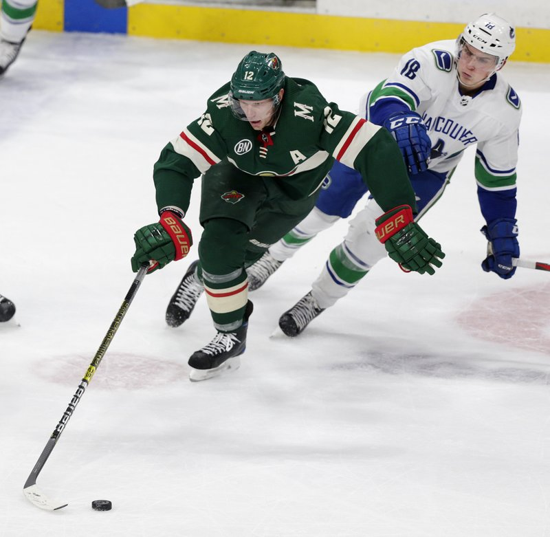 Minnesota Wild center Eric Staal (12) controls the puck against Vancouver Canucks right wing Jake Virtanen (18) during the second period of an NHL hockey game Thursday, Nov. 15, 2018, in St. Paul, Minn. (AP Photo/Andy Clayton-King)