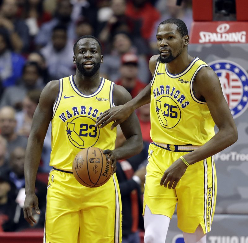 Golden State Warriors' Kevin Durant (35) pats Draymond Green (23) on the chest after a turnover during the second half of an NBA basketball game against the Houston Rockets Thursday, Nov. 15, 2018, in Houston. (AP Photo/David J. Phillip)