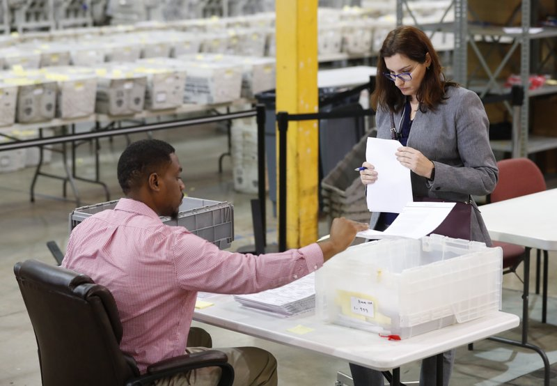 A Republican party observer, right, watches as an employee at the Palm Beach County Supervisor Of Elections office goes through a stack of damaged ballots, Thursday, Nov. 15, 2018, in West Palm Beach, Fla.  A federal judge slammed Florida on Thursday for repeatedly failing to anticipate election problems, and said the state law on recounts appears to violate the U.S. Supreme Court ruling that decided the presidency in 2000.  (AP Photo/Wilfredo Lee)