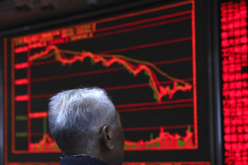 An investor monitors stock prices in Beijing, China, Friday, Nov. 16, 2018.  Shares were mixed in early trading in Asia on Friday on revived concerns over the prospects for a breakthrough in trade tensions between the U.S. and China. (AP Photo/Ng Han Guan)