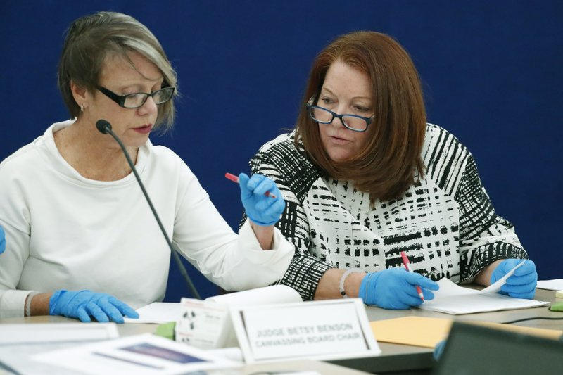 Canvassing Board chair Judge Betsy Benson, left, and board member Judge Deborah Carpenter-Toye, examine ballots with over or under votes after a hand recount, Friday, Nov. 16, 2018, Broward County Supervisor of Elections office in Lauderhill, Fla. Under state law, a hand review is required when the victory margin is 0.25 percentage points or less. (AP Photo/Wilfredo Lee)