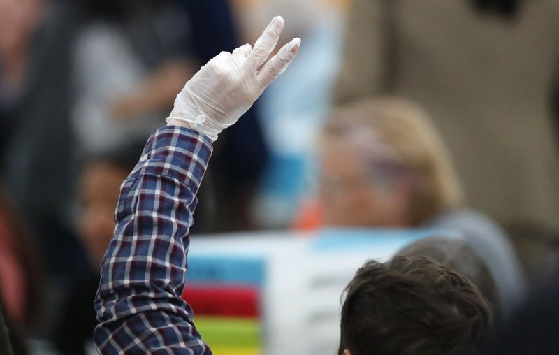 A worker at the Broward County Supervisor of Elections office signals for help during a hand recount, Friday, Nov. 16, 2018, in Lauderhill, Fla. A hand recount began Friday in Florida's acrimonious U.S. Senate contest after an initial review by ballot-counting machines showed Republican Gov. Rick Scott and Democratic Sen. Bill Nelson separated by fewer than 13,000 votes. (AP Photo/Wilfredo Lee)