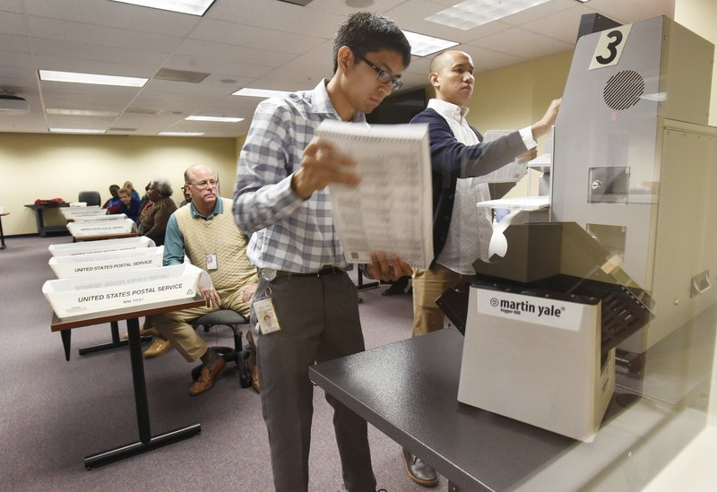 Supervisor of Elections employees put the first batch of mail in ballots into the counting machine to sort them by contested race as the Duval County Supervisor of Elections office began the hand recount of the Florida Senate and Agriculture Commissioner's race at their Imeson Park facility in Jacksonville, Fla.,  Friday, Nov. 16, 2018.  (Bob Self /The Florida Times-Union via AP)