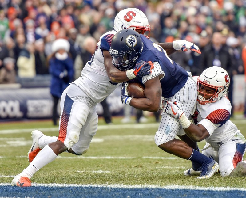 Notre Dame running back Dexter Williams, center, crosses the goal line to score the first half of an NCAA college football game against Syracuse, Saturday, Nov. 17, 2018, at Yankee Stadium in New York. (AP Photo/Howard Simmons)