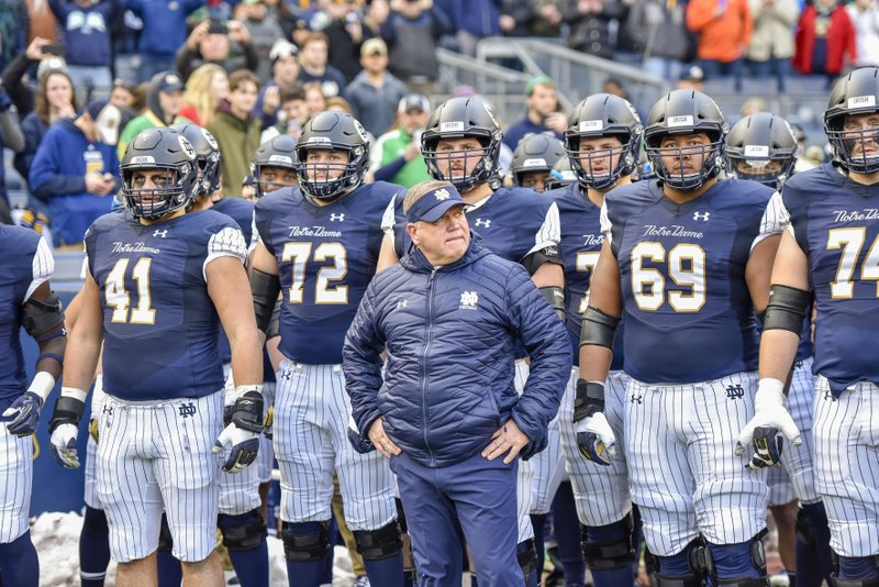 Notre Dame head coach Brian Kelly stands with his team before an NCAA college football game against Syracuse, Saturday, Nov. 17, 2018, at Yankee Stadium in New York. (AP Photo/Howard Simmons)