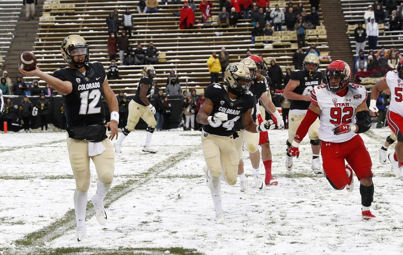 Colorado quarterback Steven Montez, left, limps to the sideline as he throws a pass as Utah defensive end Maxs Tupai pursues in the second half of an NCAA college football game Saturday, Nov. 17, 2018, in Boulder, Colo. Montez was injured while being sacked on a previous play. Utah won 30-7. (AP Photo/David Zalubowski)