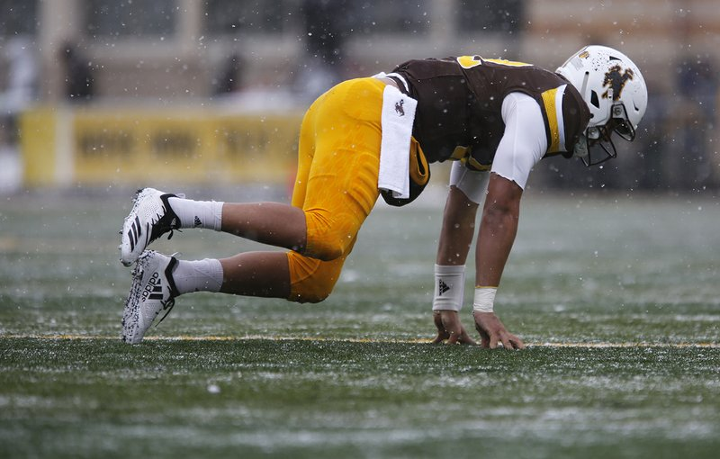 Wyoming quarterback Sean Chambers (12) crawls across the field after an injury in the first quarter against Air Force in an NCAA college football game at War Memorial Stadium Saturday, Nov. 17, 2018, in Laramie, Wyo. (Josh Galemore/The Casper Star-Tribune via AP)