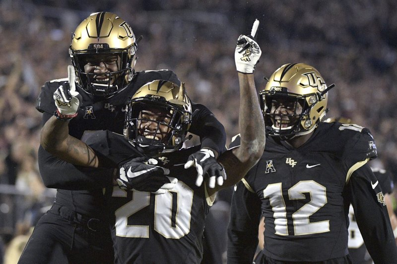 Central Florida defensive back Brandon Moore (20) is congratulated by linebacker Nate Evans, left, and linebacker Eric Mitchell after returning a blocked punt for 60 yards during the first half of an NCAA college football game against Cincinnati Saturday, Nov. 17, 2018, in Orlando, Fla. (AP Photo/Phelan M. Ebenhack)