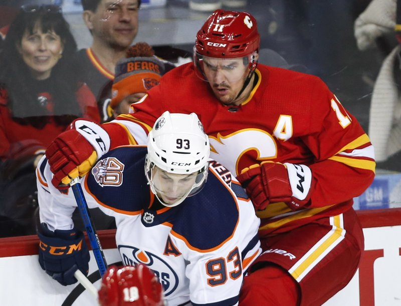Edmonton Oilers' Ryan Nugent-Hopkins, left, is checked by Calgary Flames' Mikael Backlund, of Sweden, during the second period of an NHL hockey game Saturday, Nov. 17, 2018, in Calgary, Alberta. (Jeff Macintosh/The Canadian Press via AP)
