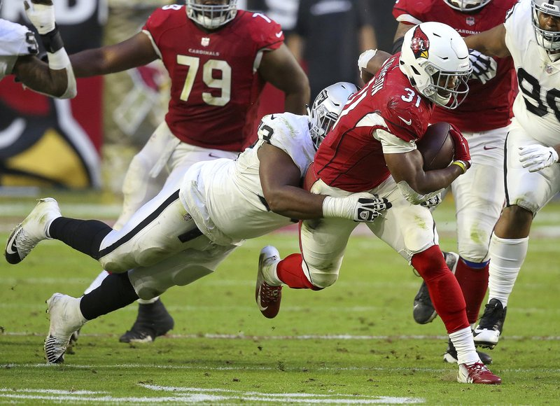 Arizona Cardinals running back David Johnson (31) is hit by Oakland Raiders defensive end Jacquies Smith (93) during the second half of an NFL football game, Sunday, Nov. 18, 2018, in Glendale, Ariz. (AP Photo/Ross D. Franklin)