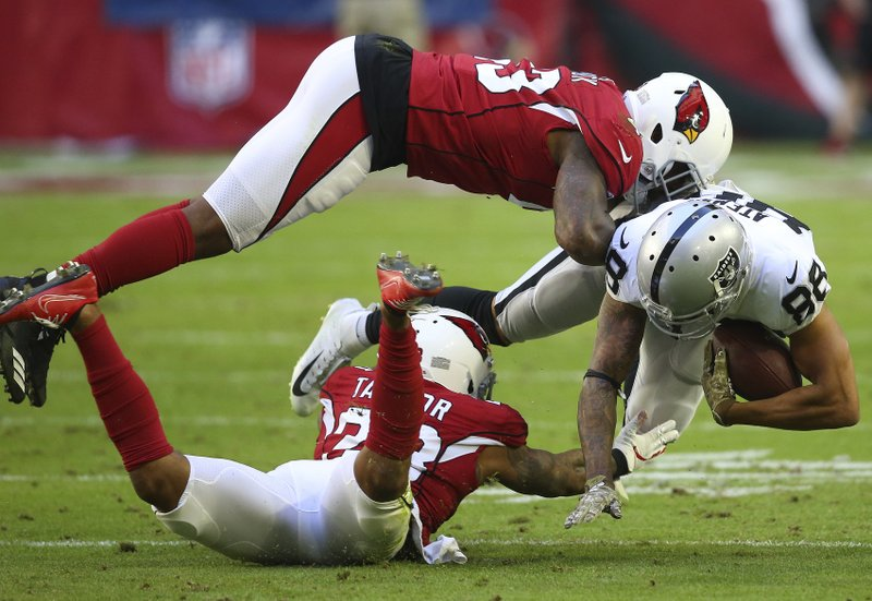 Arizona Cardinals outside linebacker Haason Reddick, top, and cornerback Jamar Taylor tackle Oakland Raiders wide receiver Marcell Ateman (88) during the first half of an NFL football game, Sunday, Nov. 18, 2018, in Glendale, Ariz. (AP Photo/Ross D. Franklin)
