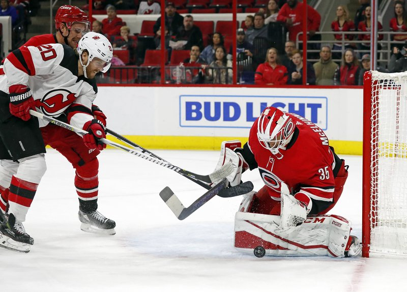 Carolina Hurricanes goaltender Curtis McElhinney (35) blocks the shot of a charging New Jersey Devils' Blake Coleman (20) with Hurricanes' Calvin de Haan (44) nearby during the first period of an NHL hockey game, Sunday, Nov. 18, 2018, in Raleigh, N.C. (AP Photo/Karl B DeBlaker)