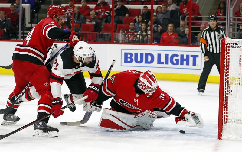Carolina Hurricanes goaltender Curtis McElhinney (35) reaches for the puck in front of New Jersey Devils' Kyle Palmieri (21) and Hurricanes' Calvin de Haan (44) during the first period of an NHL hockey game Sunday, Nov. 18, 2018, in Raleigh, N.C. (AP Photo/Karl B DeBlaker)