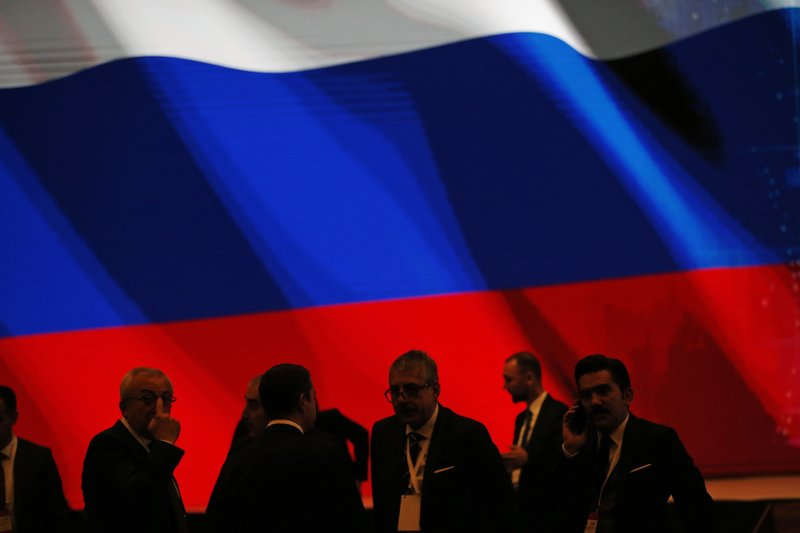 Backdropped by Russia's flag officials wait for an event to be attended by Turkey's President Recep Tayyip Erdogan and Russian President Vladimir Putin, marking the completion of one of the phases of the Turkish Stream natural gas pipeline, in Istanbul, Monday, Nov. 19, 2018. The two 930-kilometer (578-mile) lines when finished are expected to carry 31.5 billion cubic meters (1.1 trillion cubic feet) of Russian natural gas annually to European markets, through Turkish territories.(AP Photo/Lefteris Pitarakis)