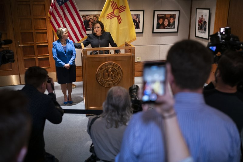New Mexico Gov. Susana Martinez, center, and U.S. Rep. Michelle Lujan Grisham, who was elected Tuesday as the state's next governor, hold a join press conference after a the two to discuss the transition at the State Capitol in Santa Fe, N.M., on Friday, Nov. 9, 2018. Martinez, a Republican and the state's first female governor, has served two consecutive terms. Lujan Grisham, a Democrat, will take office Jan. 1, 2019. (AP Photo/Craig Fritz)