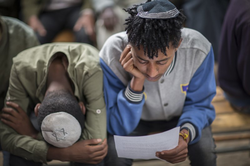Members of Ethiopia's Jewish community gather to protest the Israeli government's decision not to allow all of them to emigrate to Israel, leaving their families divided between the two countries, at the synagogue in Addis Ababa, Ethiopia Monday, Nov. 19, 2018. Representatives of the 8,000 Jews in Ethiopia urged the Ethiopian Jews living in Israel to think carefully before voting for Israel's ruling party, the Likud, over the delays in repatriation to Israel. (AP Photo/Mulugeta Ayene)