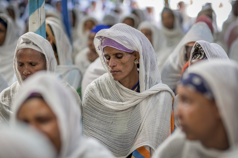 Members of Ethiopia's Jewish community, one wearing an earring of Ethiopia's flag, gather to protest the Israeli government's decision not to allow all of them to emigrate to Israel, leaving their families divided between the two countries, at the synagogue in Addis Ababa, Ethiopia Monday, Nov. 19, 2018. Representatives of the 8,000 Jews in Ethiopia urged the Ethiopian Jews living in Israel to think carefully before voting for Israel's ruling party, the Likud, over the delays in repatriation to Israel. (AP Photo/Mulugeta Ayene)