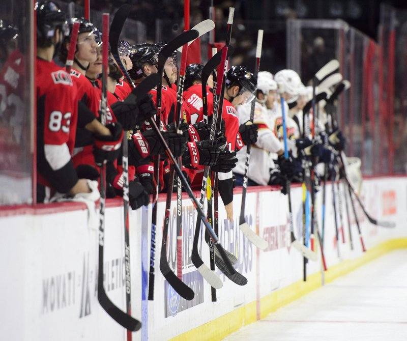 Players from the Ottawa Senators and the Florida Panthers hit their sticks on the boards as the Senators pay tribute with a message of remembrance for their equipment manager Mike Foley during first-period NHL hockey game action in Ottawa, Ontario, Monday, Nov. 19, 2018. (Sean Kilpatrick/The Canadian Press via AP)