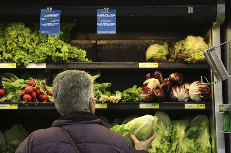 Lisa Dennis of Regent Square selects a head of green lettuce from the vegetable shelves at the East End Food Co-op Federal Credit Union Tuesday, Nov. 20, 2018, in Pittsburgh. Due to a recent consumer alert regarding a multi state E.Coli outbreak the Co-op has replaced their fresh and bagged romaine lettuce with blue signs reading,