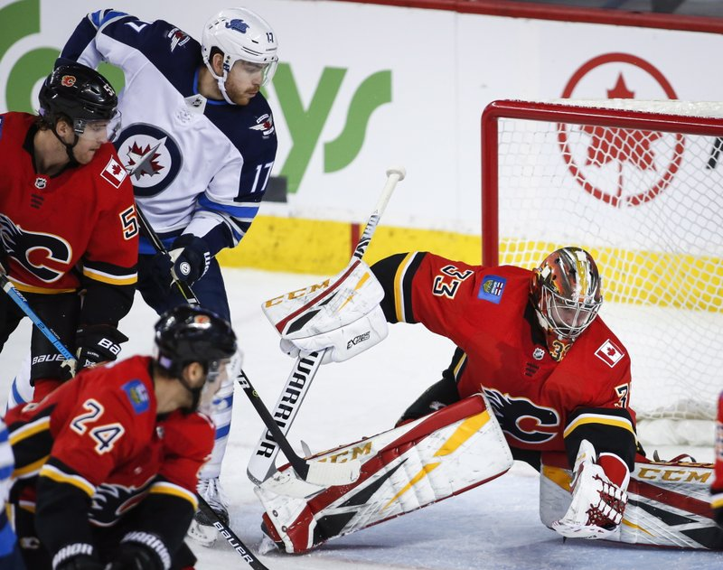 Winnipeg Jets' Adam Lowry, left, has his shot grabbed by Calgary Flames goalie David Rittich, of the Czech Republic, during the third period of an NHL hockey game Wednesday, Nov. 21, 2018, in Calgary, Alberta. (Jeff McIntosh/The Canadian Press via AP)