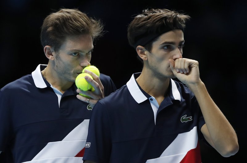 FILE - In this Wednesday, Nov. 14, 2018 file photo, Pierre-Hugues Herbert of France, right, and Nicolas Mahut of France talk tactics as they prepare to serve to Lukasz Kubot of Poland and Marceleo Melo of Brazil during their ATP World Tour Finals men's doubles tennis match at the O2 arena in London. Yannick Noah guided France to Davis Cup titles in 1991, 1996 and 2017, but he will step down after this weekend and Amelie Mauresmo will take over. For his final match as captain of France Davis Cup team, Yannick Noah has been as meticulous as ever. (AP Photo/Alastair Grant, File)