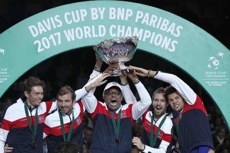 FILE - In this Sunday, Nov. 26, 2017 file photo, French captain Yannick Noah, center, holds the cup after France won the Davis Cup at the Pierre Mauroy stadium in Lille, northern France. Yannick Noah guided France to Davis Cup titles in 1991, 1996 and 2017, but he will step down after this weekend and Amelie Mauresmo will take over. For his final match as captain of France Davis Cup team, Yannick Noah has been as meticulous as ever. (AP Photo/Christophe Ena, File)