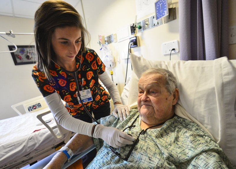 In this Wednesday, Oct. 31, 2018 photo, Lauren Duncan, a registered nurse at Brattleboro Memorial Hospital, listens to Robert Murphy's heartbeat in Brattleboro, Vt. Across Brattleboro Memorial Hospital and its clinics, the organization employs between 140 and 150 nurses. Around the world, community hospitals are facing critical nursing shortages. (Kristopher Radder/The Brattleboro Reformer via AP)