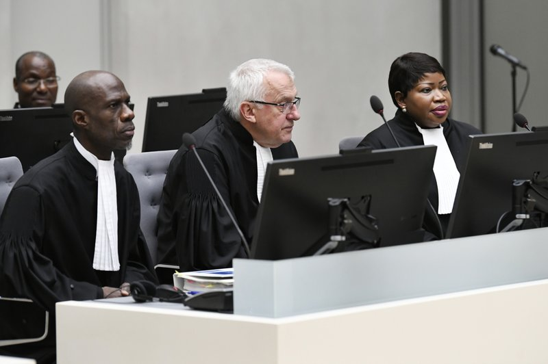 ICC's prosecutor Fatou Bensouda, right, and deputy prosecutor James Stewart, center, are seen as Alfred Yekatom, a Central African Republic lawmaker and militia leader who goes by the nickname Rambo, appears before the International Criminal Court, ICC, in The Hague, Netherlands, Friday Nov. 23, 2018. Prosecutors at the global court allege that 43-year-old Yekatom is responsible for crimes including murder, torture and using child soldiers during fighting in his country's bitter conflict. Yekatom has told the International Criminal Court that he was beaten and tortured after his arrest late last month in his country's parliament. (Piroschka van de Wouw, pool photo via AP)